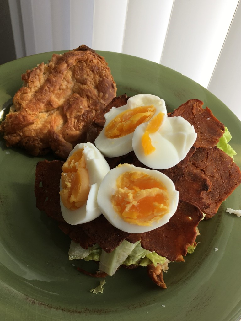 Croissant sandwich with boiled egg, lettuce, vegan bacon.