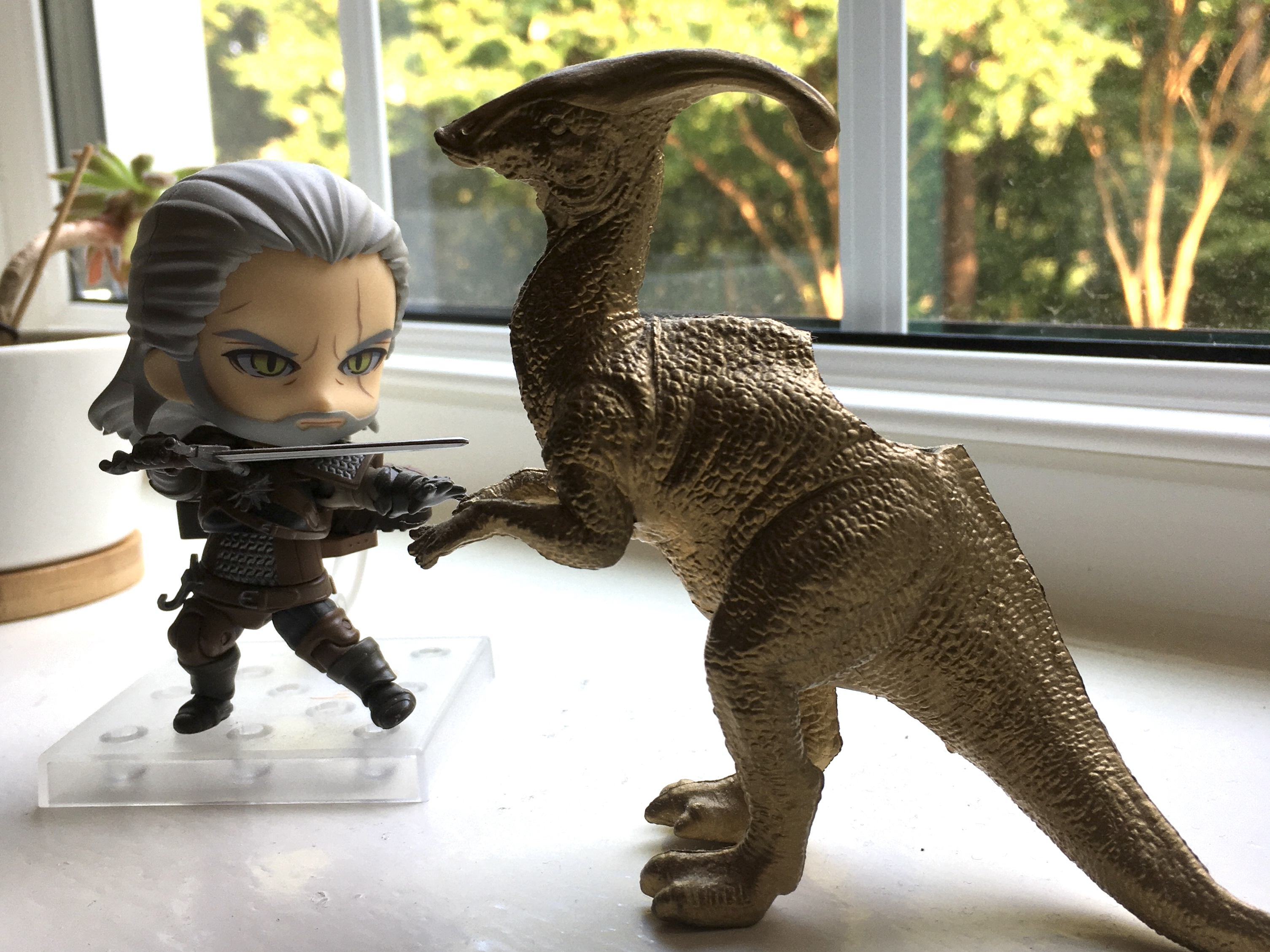 A chibi Geralt figure holding a sword and a gold plastic dinosaur planter on a windowsill, facing each other as if in battle