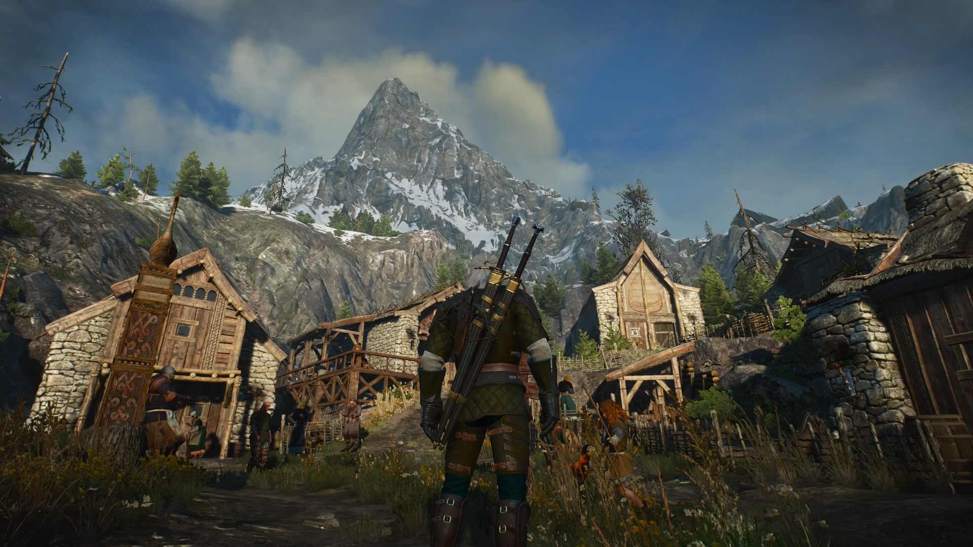Geralt from The Witcher 3 looks at a town, mountains in the background