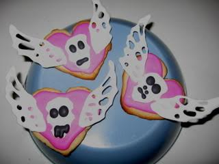 Three heart-shaped cookies on an overturned bowl. The cookies are topped with rudimentary sugar skull and wing decorations.